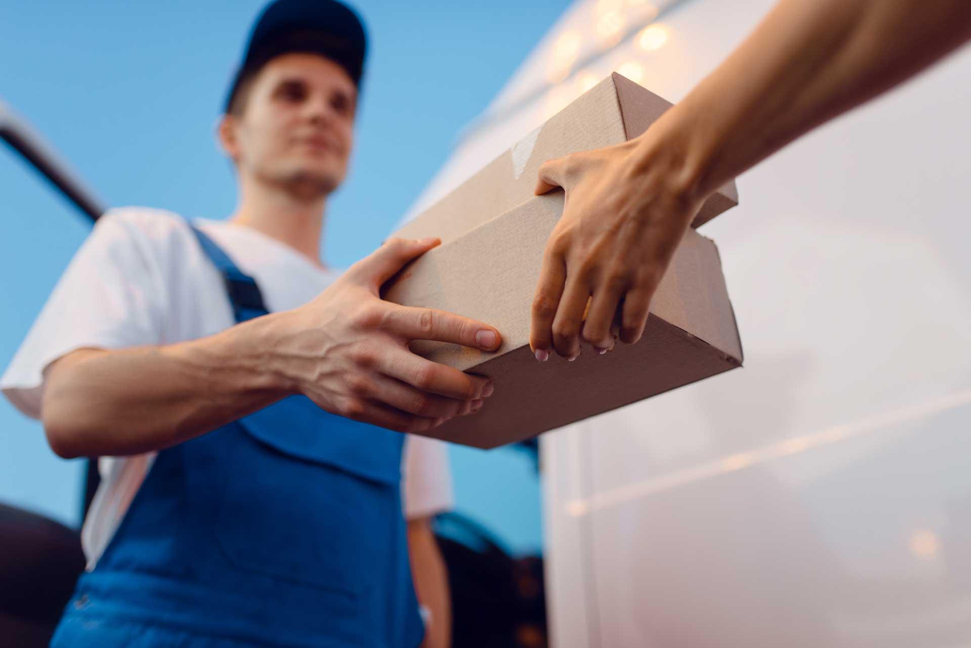 deliveryman-gives-parcel-to-female-recipient-HH3Z3T7.jpg