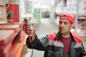Worker of contemporary large warehouse scanning qr code of tin with canned food